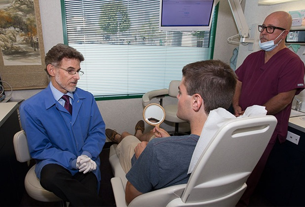 Dentist talking to dentistry patient in treatment room