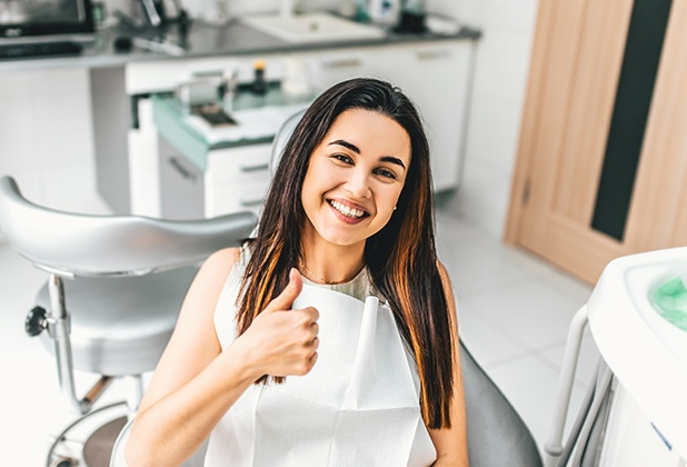Woman in dental chair smiling and giving thumbs up