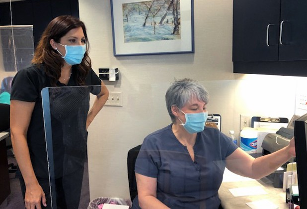 Two dental team members in consultation area wearing protective gear