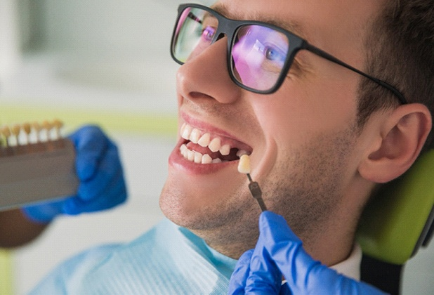 Young man smiles while getting dental implants in Beverly Hills