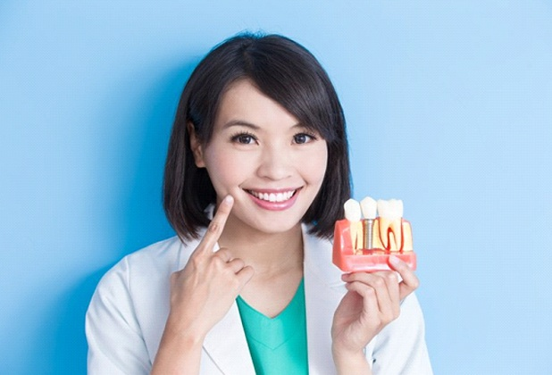 Beverly Hills implant dentist holding model implant and pointing to her smile