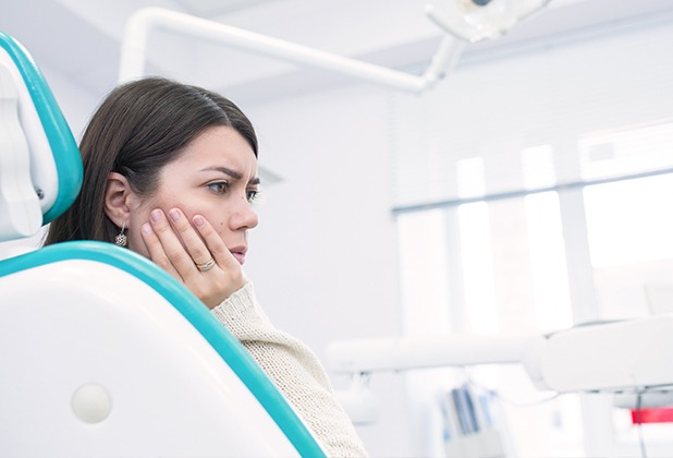 Woman holding cheek during emergency dentistry visit