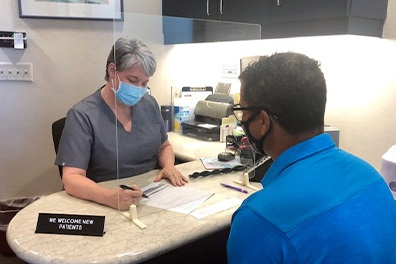 Dental team member and patient wearing safety gear during consultation