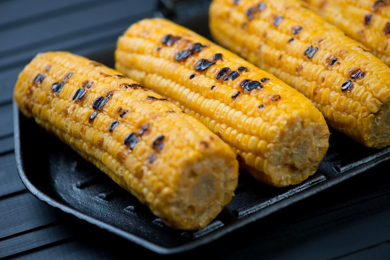 Serving grilled corn on the cob during summer